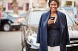 Success stylish african american woman in coat against black business suv car looking at phone. - 233227948