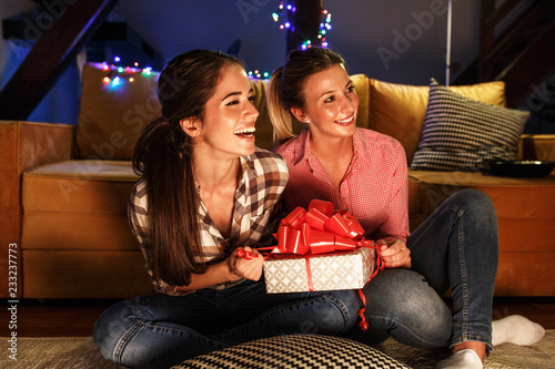 Foto Murales Young woman opens a gift which she got from her friend.Christmas concept.