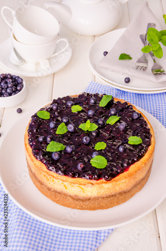 Wall mural Delicious cream cheesecake with lemon zest and blueberry jam on a plate on a white wooden background