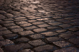 Wet illuminated paved road with cobblestone in the night - 233250578