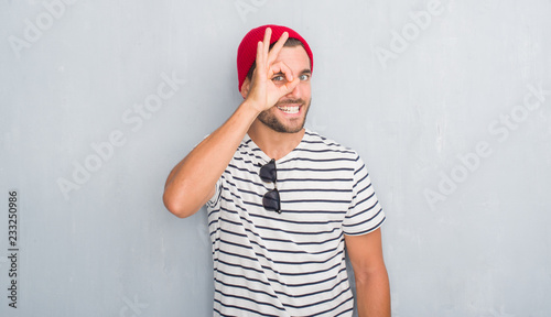 Leinwandbild Motiv Handsome young hipster man over grey grunge wall wearing navy t-shirt and wool cap doing ok gesture with hand smiling, eye looking through fingers with happy face.