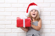 Little girl holding gift box on brick wall background