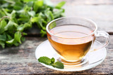 Cup of tea with mint leafs on wooden table - 233252303