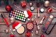 Makeup cosmetics with christmas baubles and santa hat on wooden table