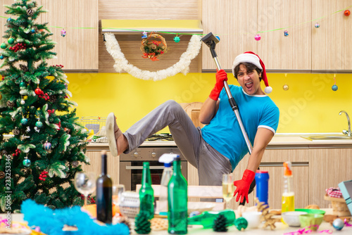 Leinwanddruck Bild Young man cleaning kitchen after Christmas party
