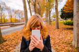 Girl using cellphone in urban autumn surroundings. © astrosystem