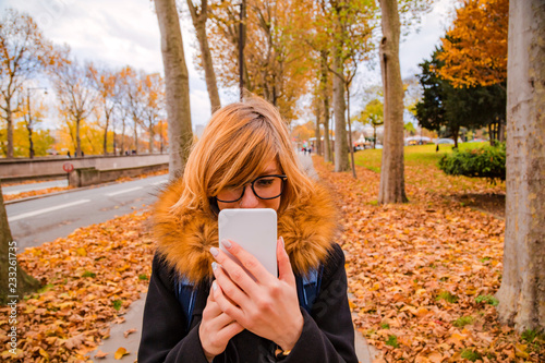 Girl using cellphone in urban autumn surroundings.