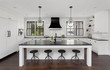 Beautiful Kitchen in New Luxury Home: Features White Woodwork and Cabinets, and Black Island, Countertops, and Hood.