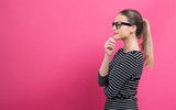 Young woman in a thoughtful pose on a pink background - 233266903