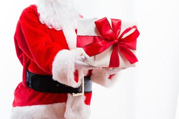 Santa holding a Christmas gift isolated on white background