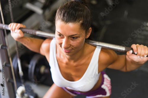 Wall mural young woman exercising with barbell