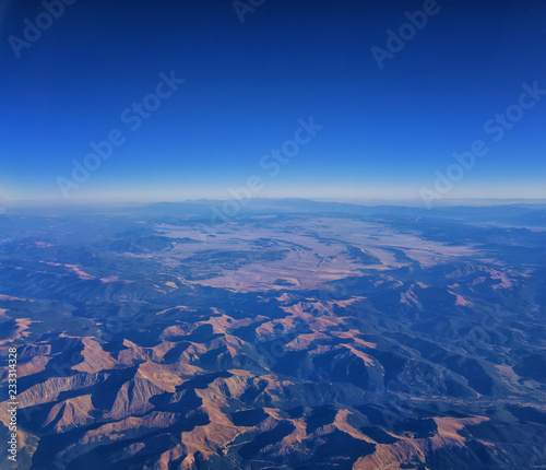 Aerial view of topographical Rocky Mountain landscapes on flight over Colorado and Utah during autumn. Grand sweeping views of rivers, mountain and landscape patterns. Top view, Rockies and Wasatch - 233314328