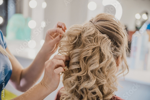 female hairdresser does hair blonde girl in a beauty salon, the process of creating hairstyles