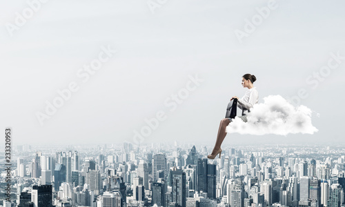 Businesswoman or accountant on cloud floating high above modern