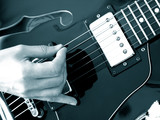 close up of hand playing black vintage electric jazz guitar hollow body