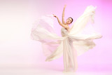 Young graceful female ballet dancer or classic ballerina dancing at pink studio. Caucasian model on pointe shoes - 233347378