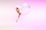 Young graceful female ballet dancer or classic ballerina dancing at pink studio. Caucasian model on pointe shoes - 233347567