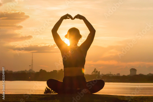 Poster Young woman practicing yoga on the park at sunset, Silhouette