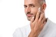 Leinwanddruck Bild - adult handsome man in bathrobe applying beauty cream on face isolated on white