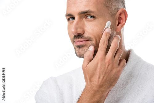 Leinwanddruck Bild adult handsome man in bathrobe applying beauty cream on face isolated on white