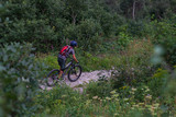 Cyclist in Red Riding the Bike on the Autumn Rocky Trail at Sunset. Extreme Sport and Enduro Biking Concept