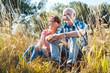 Leinwandbild Motiv Senioren Paar sitzt im Gras und hat Spaß am Sommer