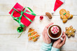 Leinwandbild Motiv Christmas hot beverage ideas, girl drinking hot chocolate with marshmallow decorate with snowflake, hands in the picture, top view, copy space, with christmas decorations