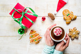 Christmas hot beverage ideas, girl drinking hot chocolate with marshmallow decorate with snowflake, hands in the picture, top view, copy space, with christmas decorations
