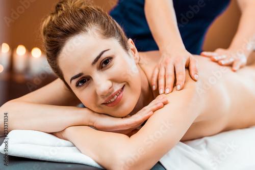 Leinwandbild Motiv beautiful happy young woman smiling at camera while having massage in spa