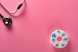 top view daily doses pills in a plastic container and a stethoscope on pink background - 233371562