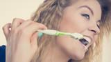 Woman brushing cleaning teeth - 233380976