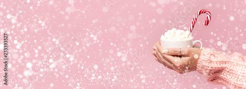 Kobiece ręce w sweter z dzianiny gospodarstwa Puchar marshmallows i Boże Narodzenie candy trzciny na różowym tle Mieszkanie świeckich kopia przestrzeń. Zimowe tradycyjne jedzenie Uroczysty wystrój uroczystości przedstawia święto Bożego Narodzenia