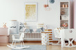 Leinwanddruck Bild - Wooden rocking horse, white and gold paper bags and white wooden crib in cozy baby nursery with painting on the wall