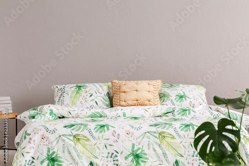 Złota poduszka umieszczona na łóżku typu king size z pościelą z litego drewna w prawdziwym zdjęciu wnętrza pokoju z szarą ścianą