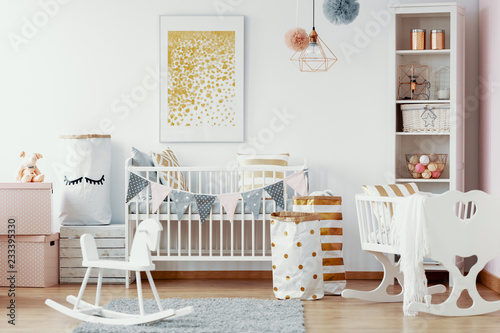 Leinwanddruck Bild Wooden rocking horse, white and gold paper bags and white wooden crib in cozy baby nursery with painting on the wall