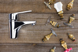top view of water mixer and various plumbing valves on rustic wooden tabletop - 233398996