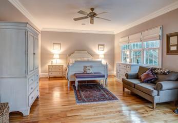 Elegant bedroom with hard wood floors and tasteful furniture