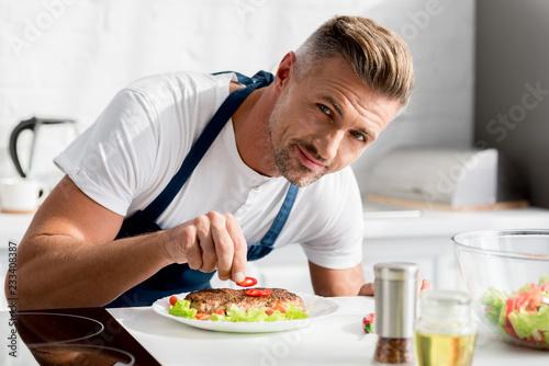 Leinwandbild Motiv adult man decorating cooked steak with chili pepper