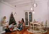 Happy people celebrating Christmas and New Year by fir-tree at home and playing guitar - 233409528