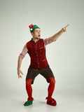 The happy smiling friendly man dressed like a funny gnome or elf pointing to left on an isolated gray studio background. The winter, holiday, christmas concept - 233409576