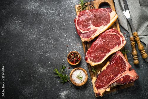 Leinwanddruck Bild Raw meat beef steak on black top view.