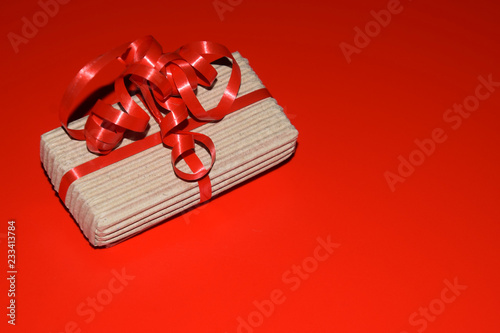 present box christmas background with copy space, top view of gift box wrapped in cardboard packaging with red ribbon on red surface