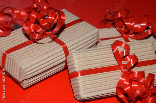 birthday or christmas present boxes, top view of gift box wrapped in cardboard packaging with red ribbon on red surface