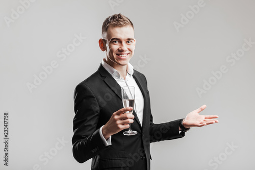 Foto Murales Handsome man in a business suit smiles and holds glass of champagne  on a white background. Party time