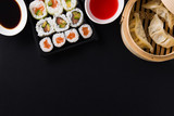 Dumplings or gyoza served in traditional steamer and sushi on black background. Top view. Copyspace © chandlervid85