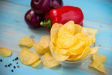 Potato chips in bowl on a blue wooden background - 233421752