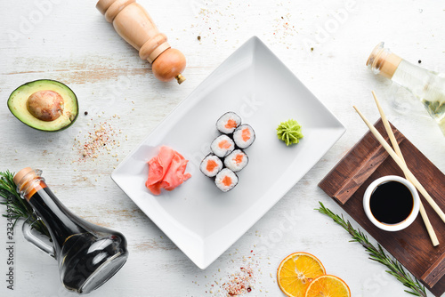 Sushi roll maki with salmon. Japanese cuisine. Top view. On a white wooden background.