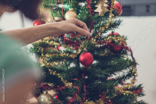 Retro image of a woman hanging shiny red holiday bauble on Christmas tree - 233442337