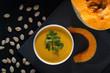 Pumpkin soup and pumpkin seeds on a black wooden table. - 233447385