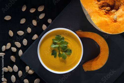 Foto Murales Pumpkin soup and pumpkin seeds on a black wooden table.